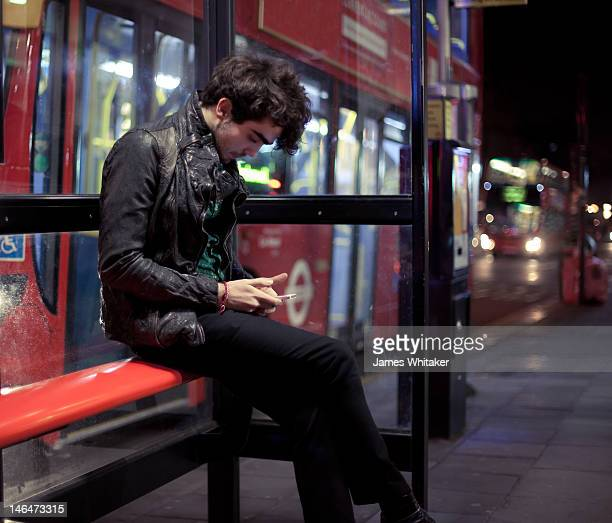 Young man checks phone at bus stop