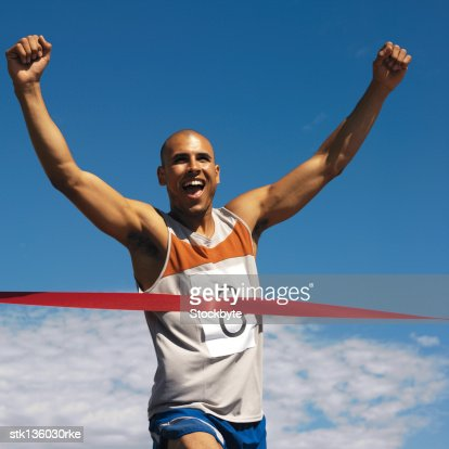 young man cheering at completing race : Stock Photo