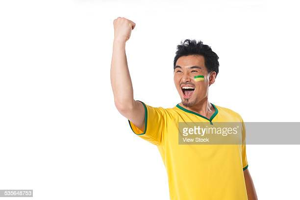 Young man cheering with arm raised