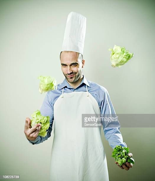 Young Man Chef juggling lettuce heads