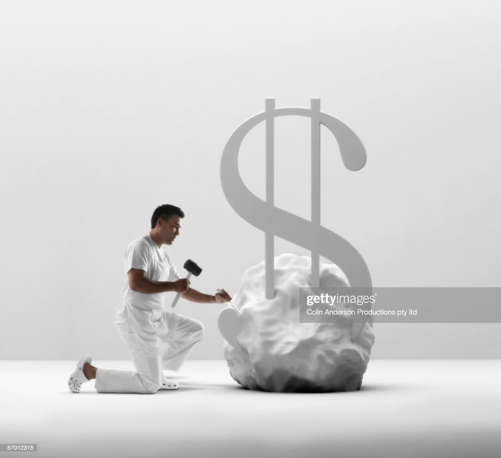 Young man chiseling a dollar sign out of stone