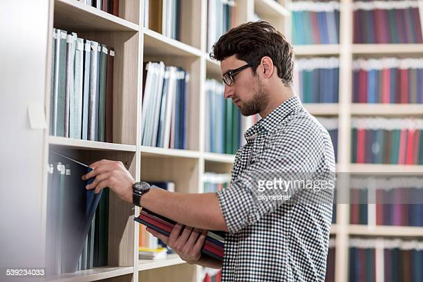 Young man choosing books in the library.