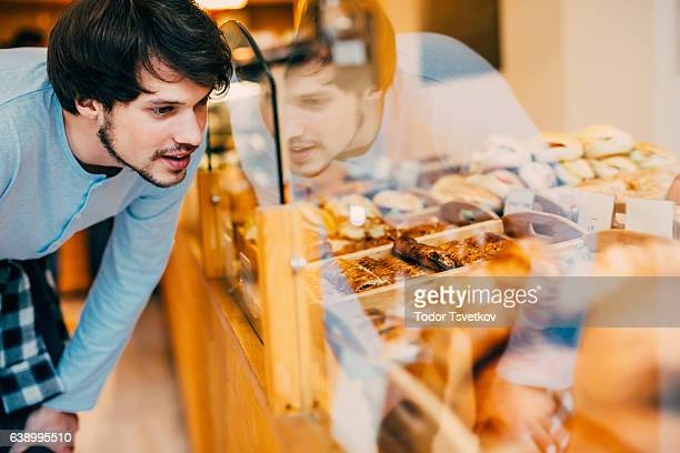 Young man choosing what to buy at a bakery