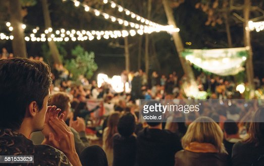Young man clapping in night music festival