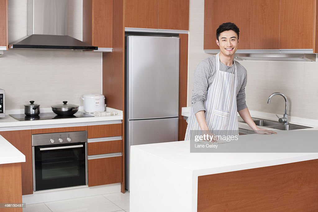 Young man cleaning kitchen : Stock Photo