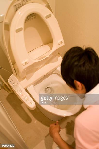 Young man cleaning toilet bowl