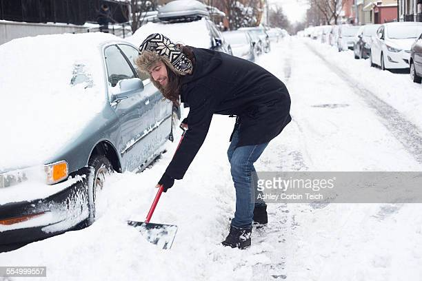 Young man clearing snow from road with shovel