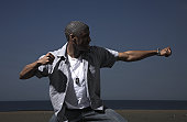 Young man clenching fists, striking martial pose at beach