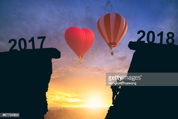 Young man climbing between 2017 and 2018 years with hot air balloon.