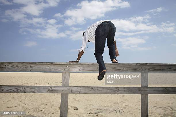 Young man climbing over fence to beach, rear view