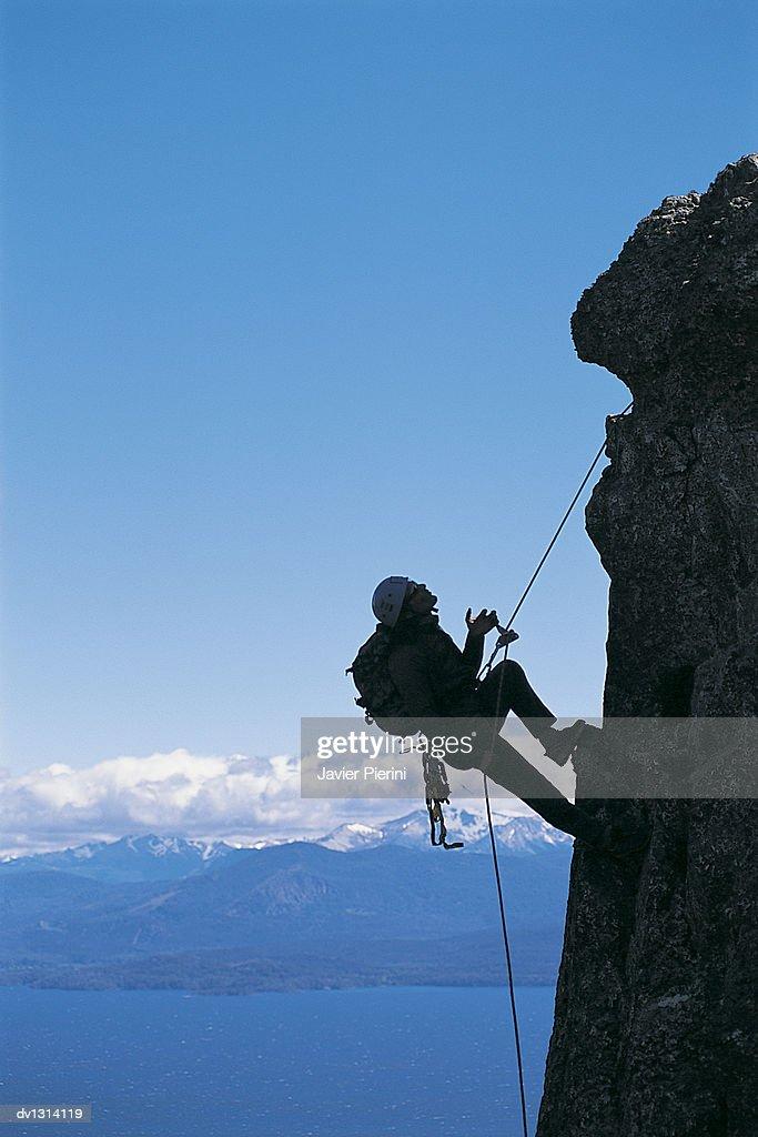 Young Man Climbing Vertical Rock Face High Above Valley : Stock Photo