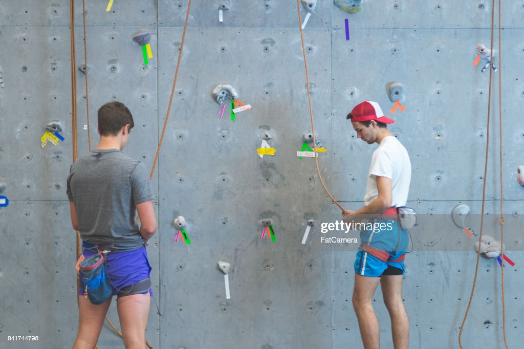 Young man climbs indoor rock wall : Stock Photo