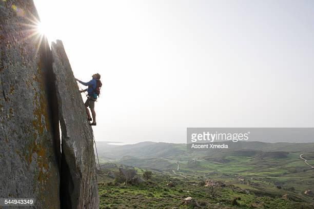 Young man climbs steep rock, towards sunlight