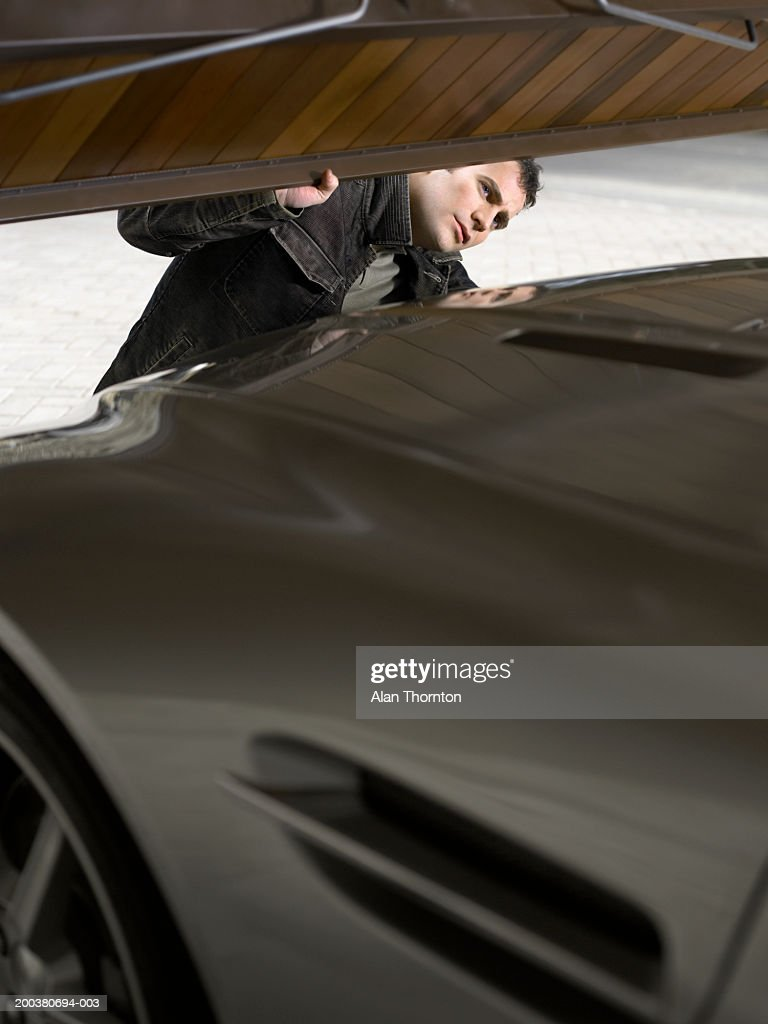Young man closing garage door on car : Stock Photo