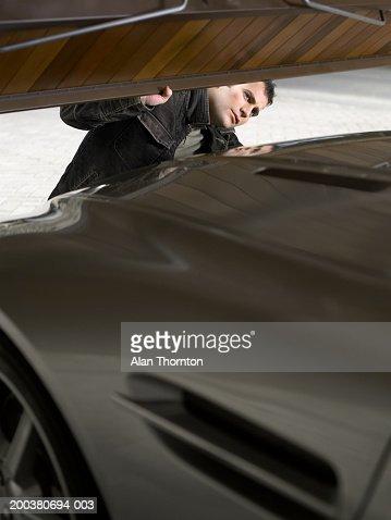 Young man closing garage door on car : ストックフォト