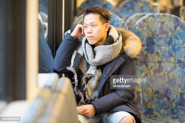 Young man commuting in train