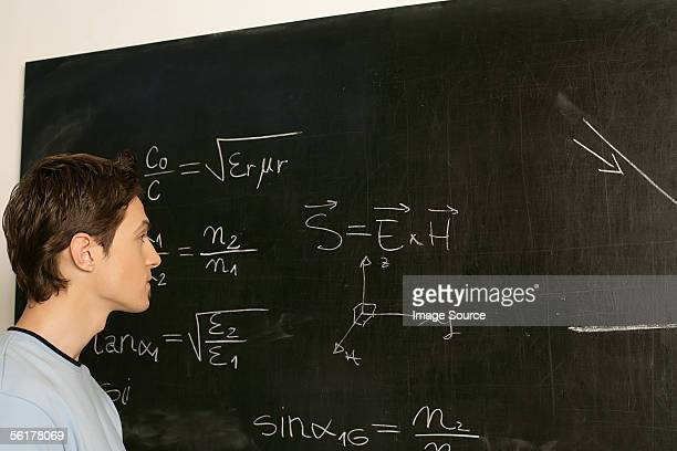 Young man contemplating equation on blackboard