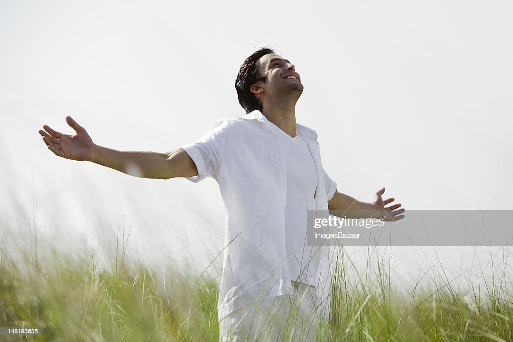 Young man contemplating on meadow : Stock Photo