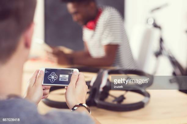Young man controlling drone by smart phone