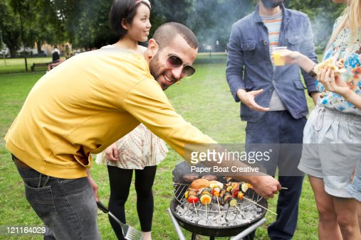 A young man cooking burgers on a BBQ in summer : Stock Photo