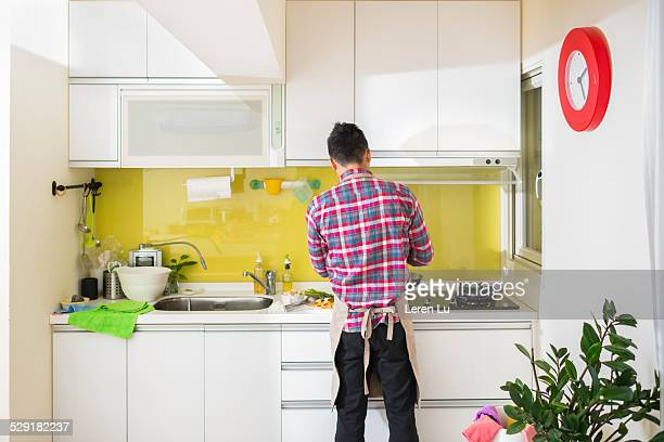 Young man cooking dinner in kitchen at home.