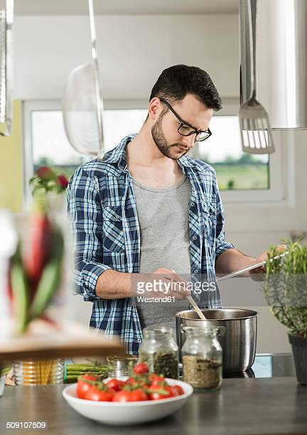 Young man cooking in kitchen at home