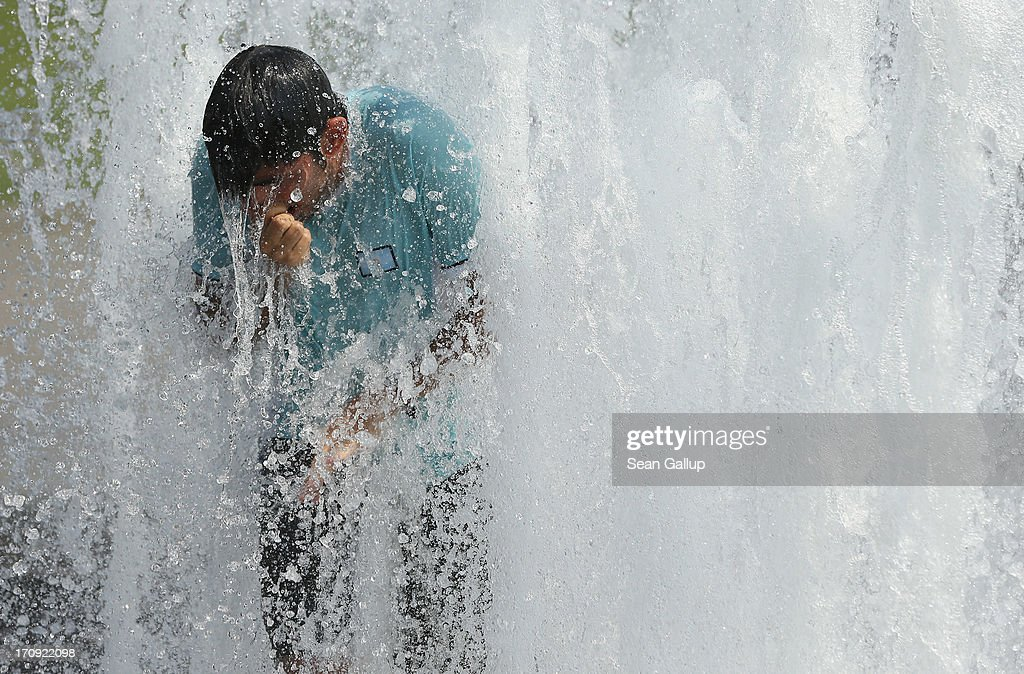 A young man cools off in a fountain on a scorching hot summer day in the city center on June 20, 2013 in Berlin, Germany. Central Europe is in the grips of a heat wave in which temperatures in some regions have reached up to 38 degrees celsius.