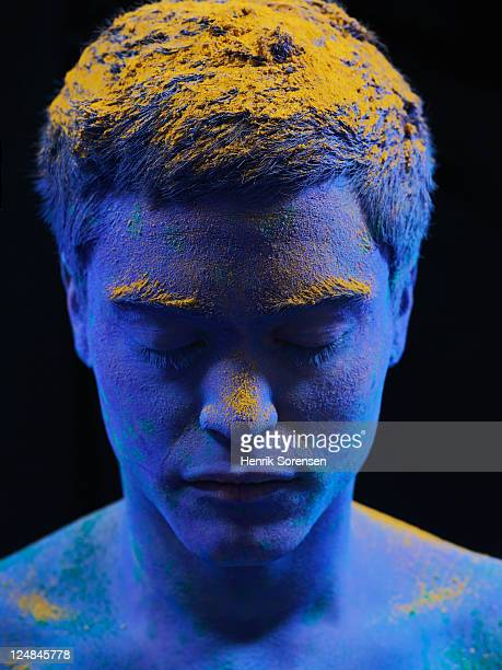 young man covered by colored powder