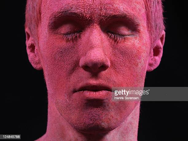 young man covered by red powder