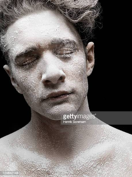 Young man covered by white powder