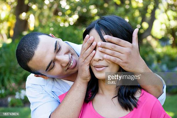Young man covering woman's eye