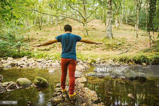 Young man crossing river