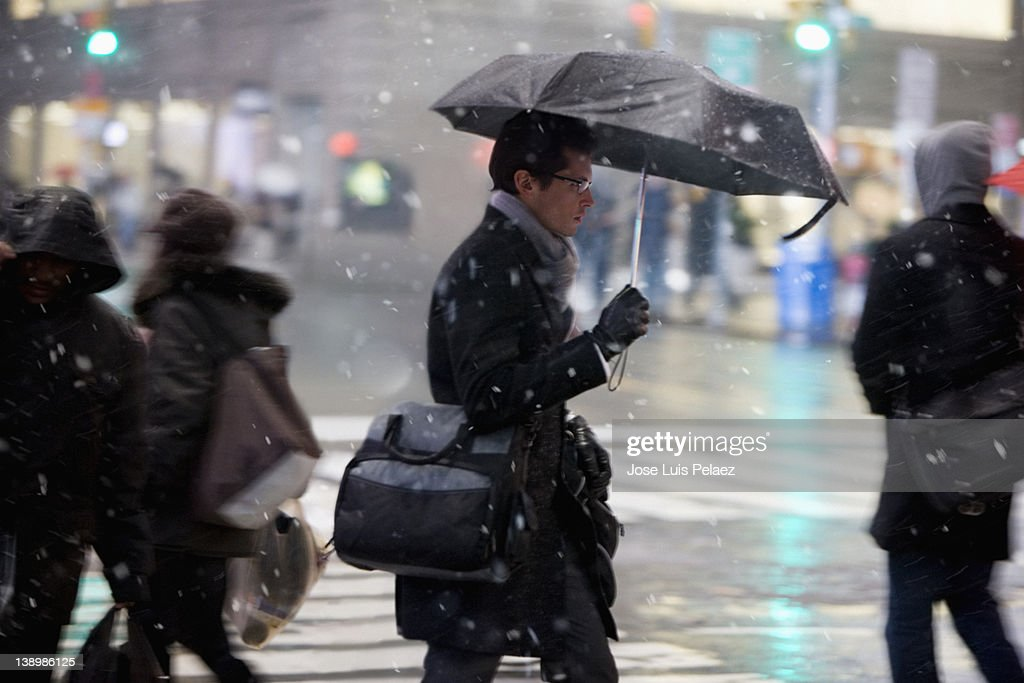 Young man crossing street during snow : Stock Photo