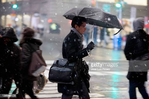 Young man crossing street during snow