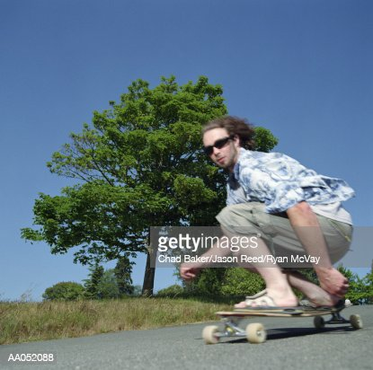 Young man crouching down on longboard, low angle view : Stock Photo