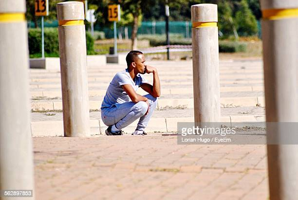 Young Man Crouching While Contemplating On Street
