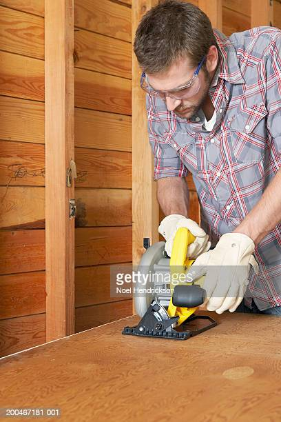 Young man cutting plywood with circular saw