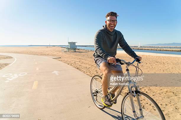 Young man cycling along pathway at beach