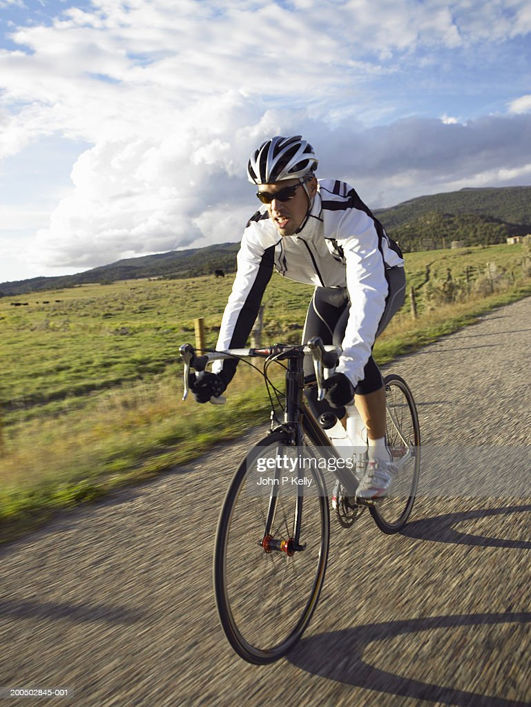Young man cycling on country road (blurred motion) : Stock Photo