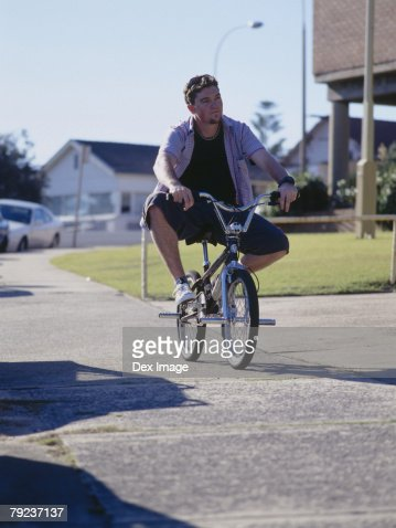 Young man cycling on pavement : Stock Photo
