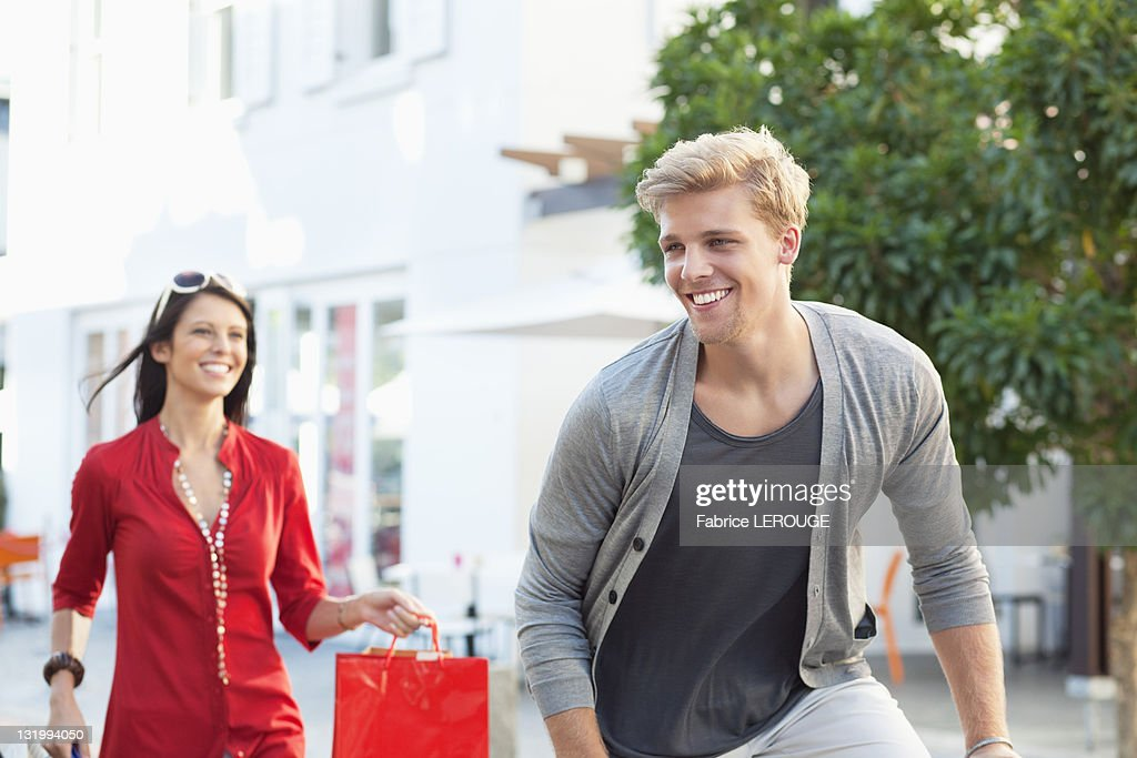 Young man cycling with his girlfriend running after him with shopping bags : Stock Photo