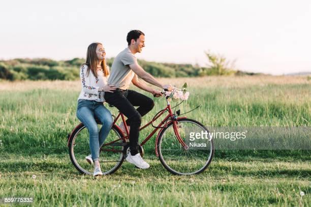 Junger Mann Radfahren mit Frau zu Fuß auf der Wiese