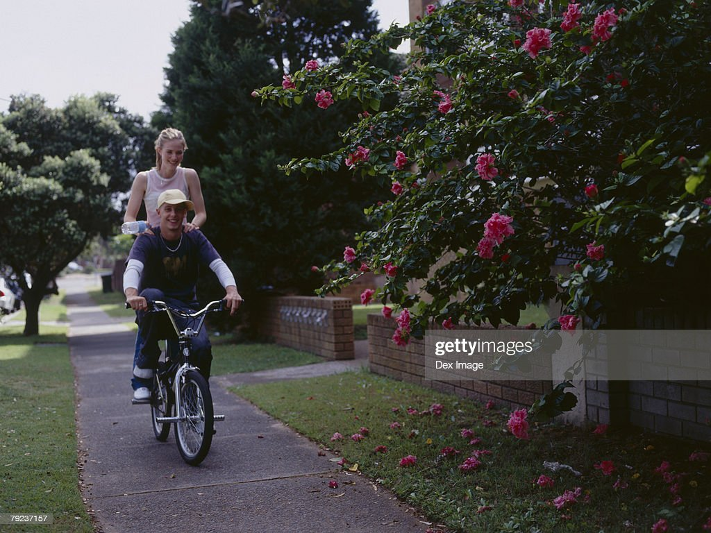 Young man cycling with young woman on back of bike : Stock Photo