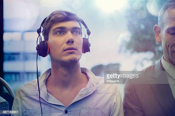 Young man daydreaming and listening to headphones on train
