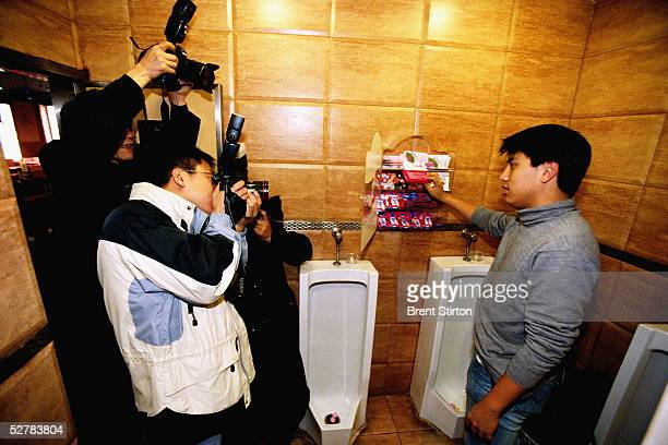 A young man demonstrates free condom availability to the Chinese media in a bar toilet November 21 2004 in Beijing The demonstration was part of an...