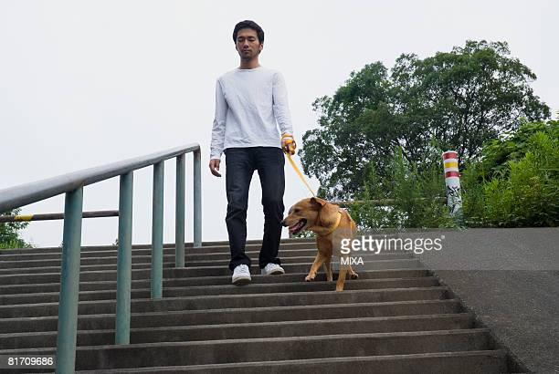 Young man descending steps with dog