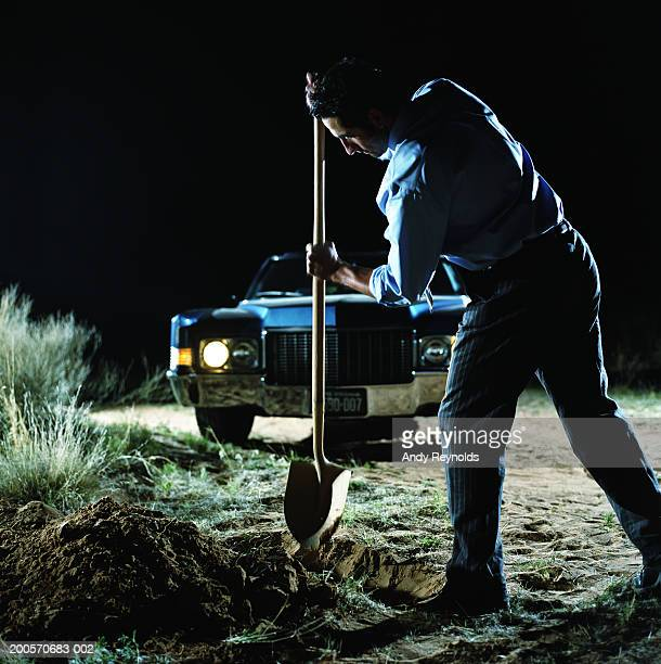 Young man digging hole in front of car in desert at night, side view