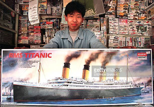 A young man displays a largescale model of the doomed luxury cruise liner the Titanic at his toy booth 08 May in Beijing China has injected over...