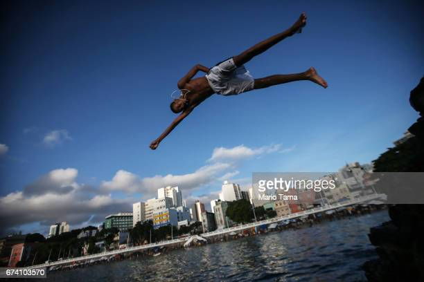 A young man dives off a pier in the Barra neighborhood in an upscale section of the city on April 19 2015 in Salvador Brazil