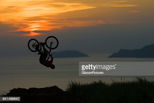 A young man does a backflip off a big jump on his mountain bike at sunset.
